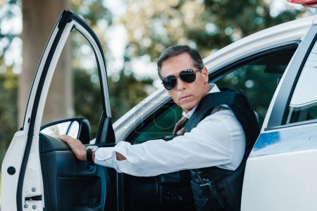 selective focus of mature policeman in bulletproof vest and sunglasses walking out from car
