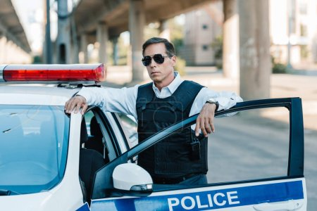 confident mature policeman in sunglasses and bulletproof vest standing near car at city street
