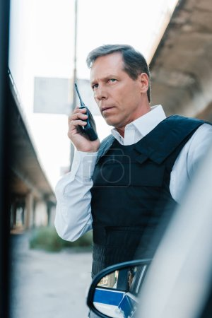 mature male police officer in bulletproof vest talking on radio set near car at street