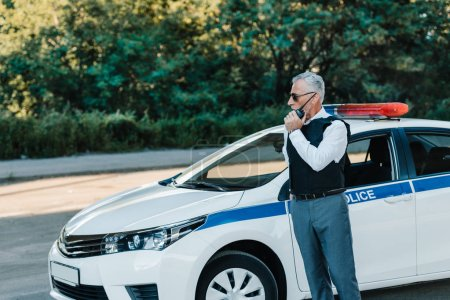 middle aged policeman in bulletproof vest talking on radio set near car at urban street