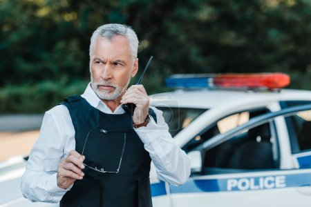 serious middle aged policeman in bulletproof vest talking on radio set near car at street