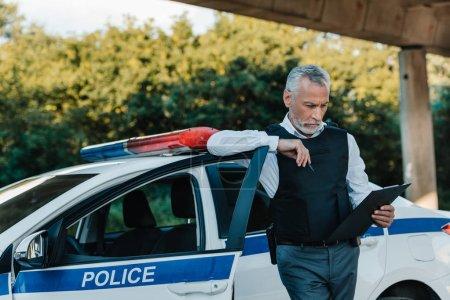 mature policeman in bulletproof vest looking at clipboard near car at street