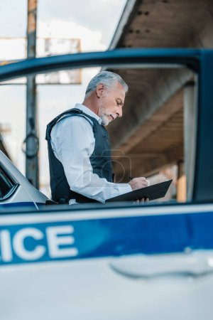 low angle view of mature policeman in bulletproof vest writing in clipboard near car at street