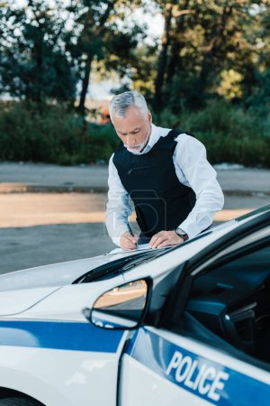 concentrated mature male police officer writing in clipboard on car at street