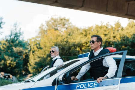 Photo for Selective focus of mature policeman in sunglasses and bulletproof vests standing near car at city street - Royalty Free Image