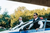 selective focus of mature policeman in sunglasses and bulletproof vests standing near car at city street