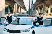 confident mature policeman in sunglasses and bulletproof vests standing near car at city street
