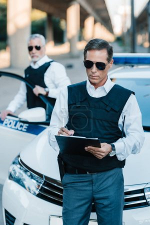Photo for Male police officer in sunglasses writing in clipboard while his colleague standing near car at street - Royalty Free Image