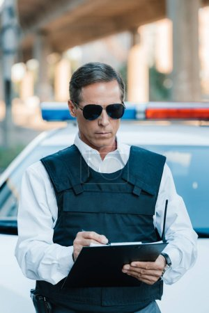 male police officer in sunglasses writing in clipboard near car at street