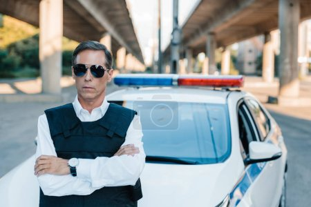 Photo for Mature policeman in sunglasses and bulletproof vest standing with crossed arms near car at street - Royalty Free Image
