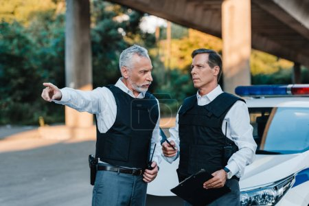 Photo for Mature male police officer pointing by finger to colleague with clipboard near car at street - Royalty Free Image