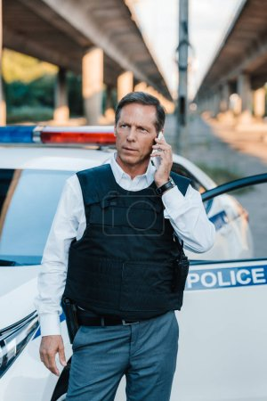 male police officer in bulletproof vest talking on smartphone near car at street