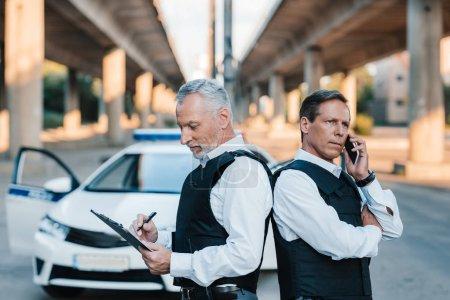 Photo pour Mature policier parler sur smartphone et debout avec collègue dos à dos alors qu'il écrit dans le presse-papiers à la rue de la ville - image libre de droit