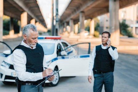 Photo pour Agent de police d'âge moyen écrit dans le presse-papiers tandis que son collègue parle sur smartphone à la rue - image libre de droit