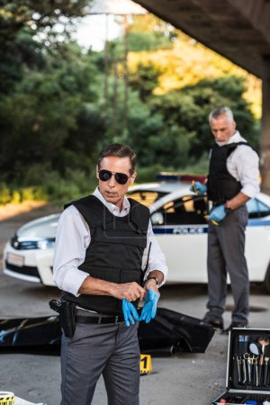 serious policeman in sunglasses putting on latex gloves while his colleague standing behind at crime scene with corpse in body bag