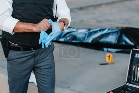 cropped image of policeman with gun in holster putting on latex gloves at crime scene with corpse in body bag
