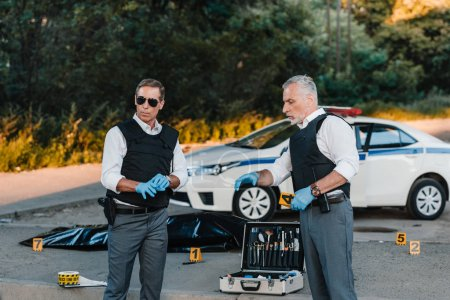 mature policeman in latex gloves pointing by finger to colleague in sunglasses standing near at crime scene with corpse in body bag