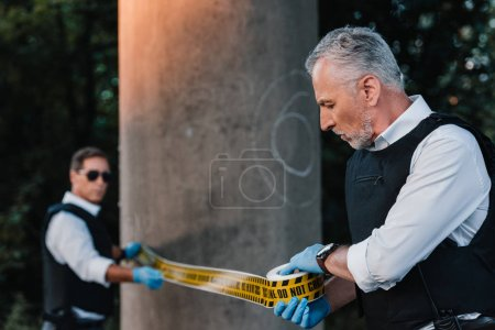 selective focus of mature male police officers in latex gloves setting police line at crime scene