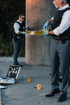 middle aged male police officers in latex gloves setting police line at crime scene