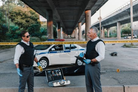 mature policeman with clipboard talking to colleague in sunglasses near corpse in body bag at crime scene