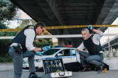 middle aged policeman holding police line above head and talking to colleague in sunglasses standing near case with investigation tools at crime scene