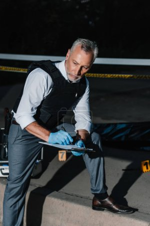 serious middle aged policeman writing in clipboard at crime scene with corpse in body bag