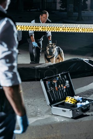 partial view of police officer standing near case with investigation tools while his colleague standing with german shepherd on leash near corpse at crime scene