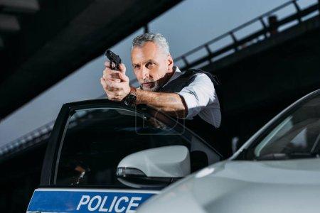 confident mature policeman aiming by gun near car at city street