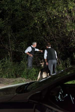 male police officer with gun pointing by finger to colleague with alsatian on leash outdoors
