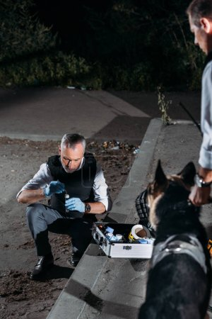 Photo for Male police officer in latex gloves collecting evidence with case for investigation tools while his colleague standing with dog on leash at crime scene - Royalty Free Image