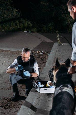 Foto de Hombre policía en guantes de látex recolección de evidencia con el caso de herramientas de investigación mientras que su colega de pie con perro con correa en la escena del crimen - Imagen libre de derechos