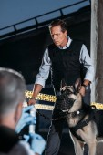 selective focus of mature policeman with german shepherd dog on leash while his colleague sitting near at crime scene