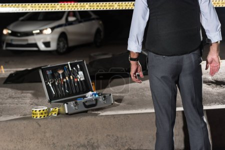 cropped image of policeman standing near cross line and case with investigation tools near corpse in body bag at crime scene
