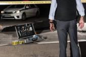 """Постер, картина, фотообои """"обрезанное изображение полицейского, стоя возле пересечь линию и случае с инструментами расследования возле трупа в тело мешок на месте преступления"""""""