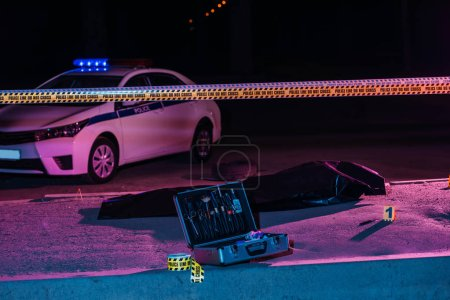 Photo for Toned picture of crime scene with police car, case with investigation tools, cross line and corpse in body bag - Royalty Free Image