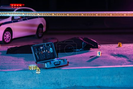 Photo for Toned picture of case with investigation tools, cross line, police car and corpse in body bag at crime scene - Royalty Free Image