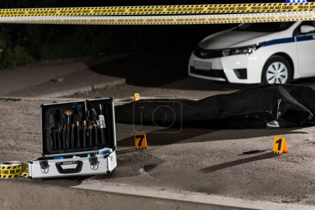 case with investigation tools, car, police line and corpse in body bag at crime scene