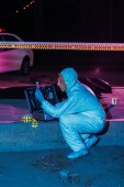 side view of focused male criminologist in protective suit and latex gloves collecting evidence at crime scene with corpse