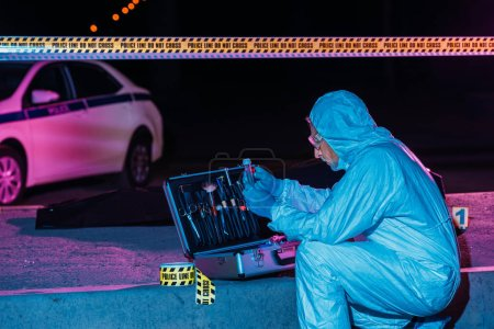 Photo for Concentrated mature criminologist in protective suit and latex gloves collecting evidence at crime scene with corpse - Royalty Free Image