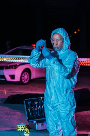 focused male criminologist in protective suit and latex gloves collecting evidence near cross line at crime scene
