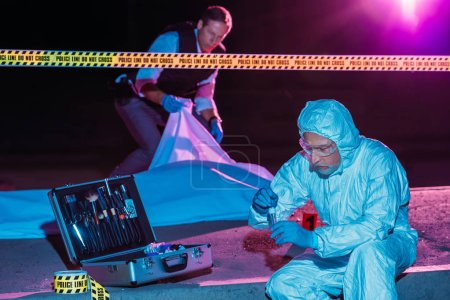 middle aged male criminologist collecting evidence while policeman covering corpse at crime scene