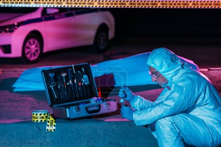 side view of male criminologist in protective suit and latex gloves putting evidence into flask by tweezers at crime scene with corpse