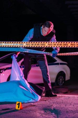 Photo pour Moyenne ans mâle policier regardant cadavre dans sac mortuaire sur scène de crime - image libre de droit