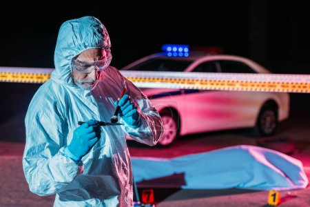 concentrated mature male criminologist in protective suit and latex gloves taking fingerprints from knife at crime scene