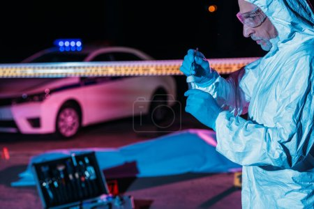 focused male criminologist in protective suit and latex gloves putting evidence into flask by tweezers at crime scene with corpse
