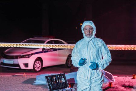 mature male criminologist in protective suit and mask looking at camera near crime scene with corpse in body bag