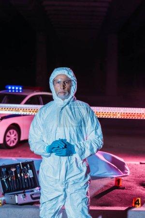 Foto de Criminólogo hombre en traje de protección y máscara mirando a cámara junto a la escena del crimen con el cadáver en bolsa de plástico y caja con herramientas de investigación - Imagen libre de derechos