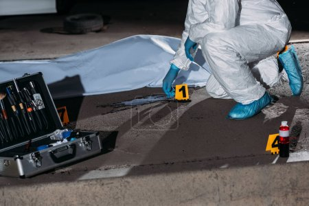 cropped image of criminologist in protective suit and latex gloves collecting evidence at crime scene with corpse