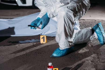cropped image of criminologist in latex gloves and protective suit holding knife above blood on ground near corpse in body bag at crime scene
