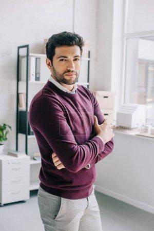 Photo pour Beau concepteur en pull bordeaux debout avec les bras croisés et regardant la caméra dans le bureau - image libre de droit